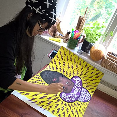 "Kiki Hitomi painting the artwork for Roger Robinson's ""Dog Heart City"" tape"
